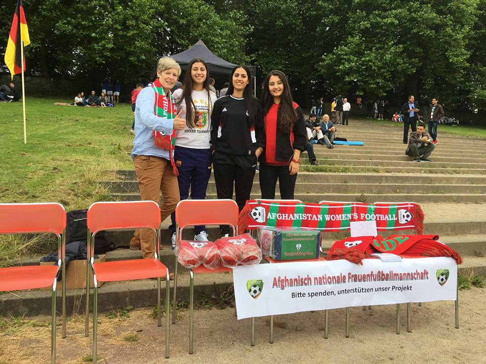 4 Members of the AFF Women's National Team stand in a park selling scarves.