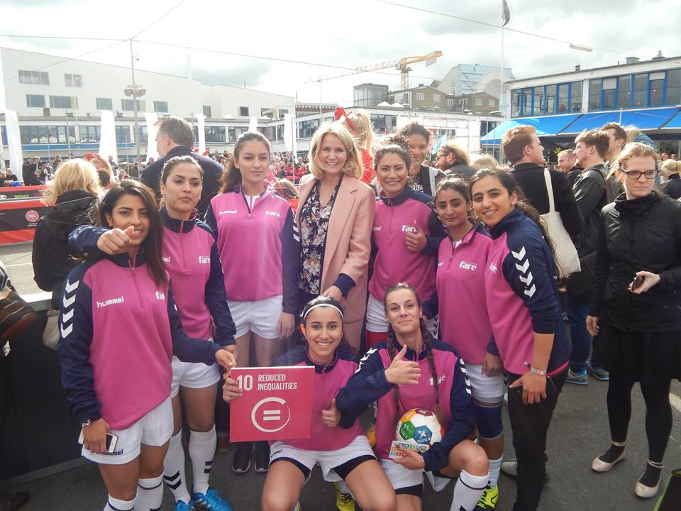 8 members of the AFF National Team wearing pink uniforms pose with the Denmark Prime Minister for a photo