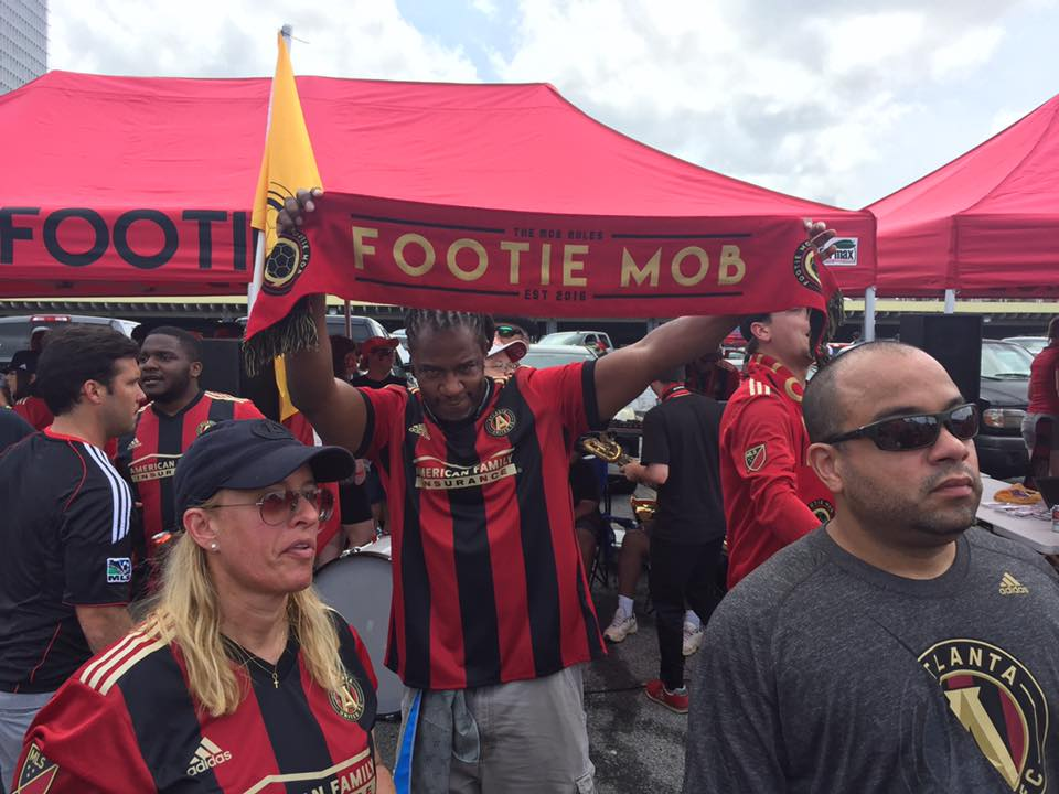 A Footie Mob member holding up a soccer scarf.