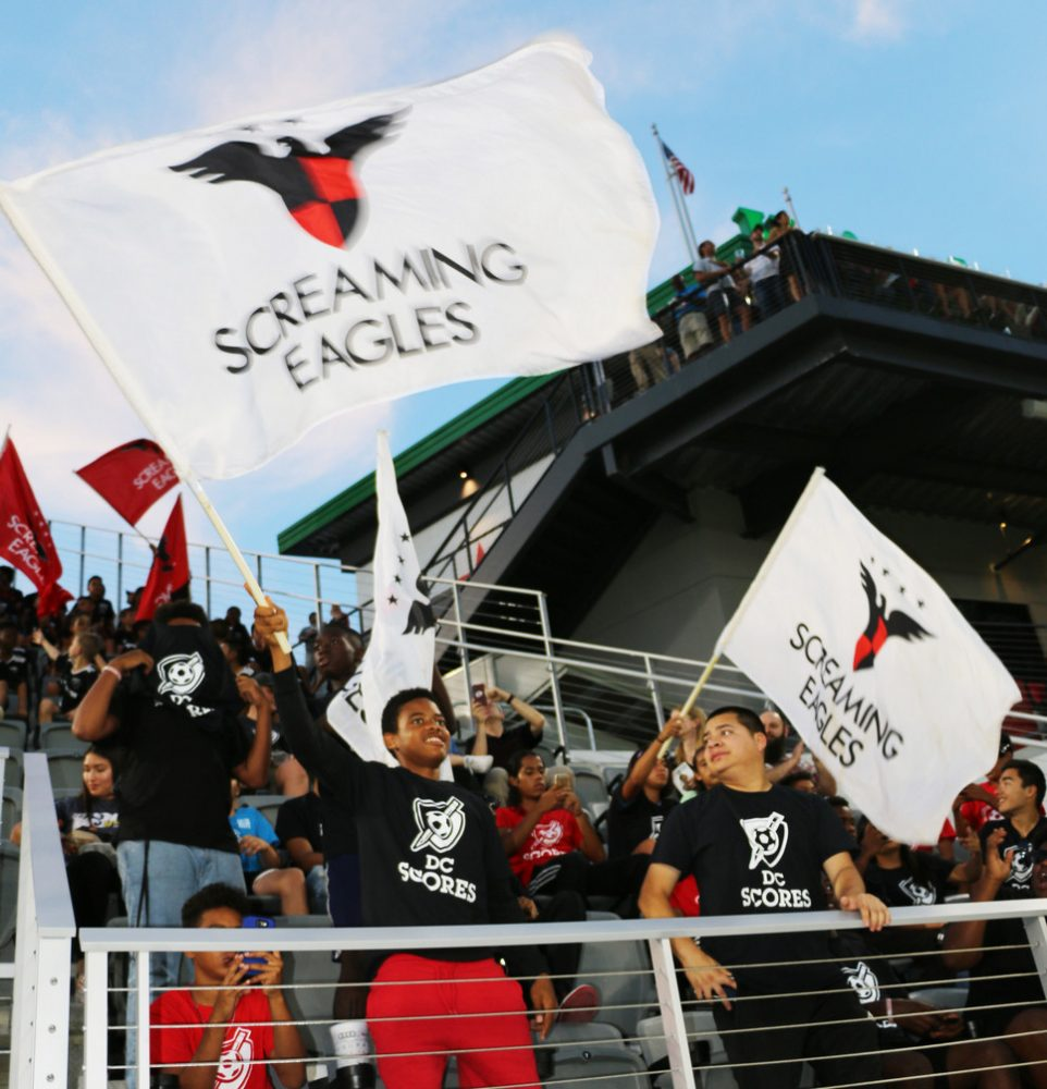 D.C. United fans raising flags to support their team.