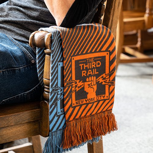 man sitting on a wooden chair with two Diehard Custom champion knit scarfs, one orange and one blue, draped over the arm rest - The Third Rail