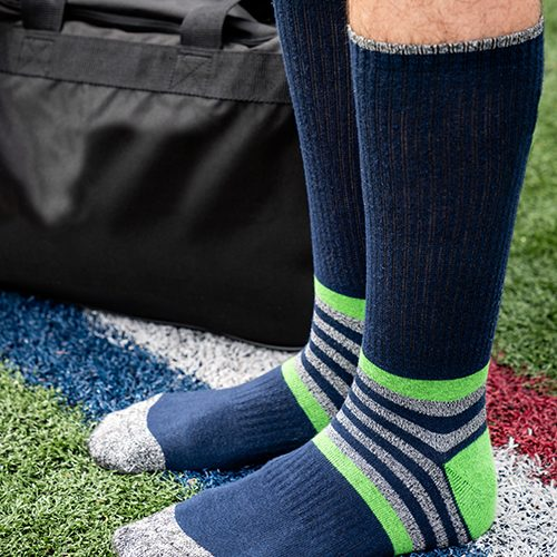 man wearing Diehard Custom blue, green and grey socks standing on a soccer field