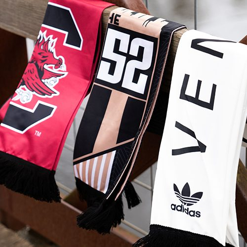three scarves draped over a bench, one red and black, black and tan and white and black adidas