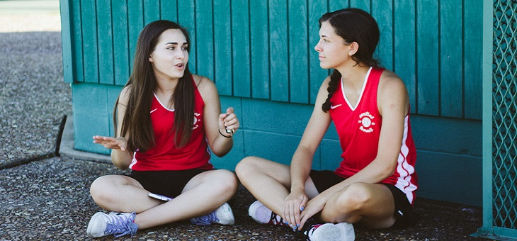 two female athletes sitting on the ground chatting.