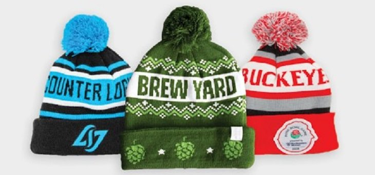 green brew yard pom beanie, blue and black striped beanie and a red, black and white Buckeye pop beanie stacked on each other designed by Diehard Custom