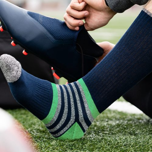 man sitting on a soccer field wearing Diehard Custom blue, grey, and green striped socks putting on cleats