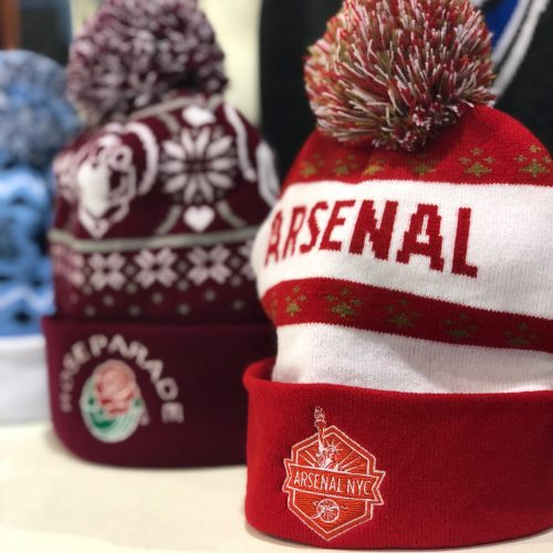 three pom beanies side by side with the red and white Arsenal NYC pom beanie in the front