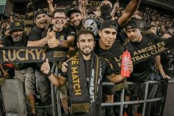 a group of men smiling holding up their black and tan Los Luckys Los Angeles custom scarves at a soccer game