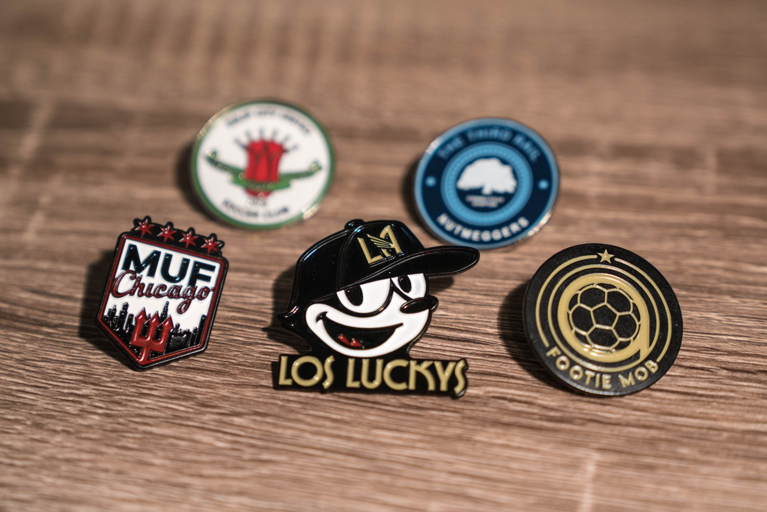 flat lay of five enamel pins on wooden table - Los Luckys, Footie Mob, Third Rail NYC, MUF Chicago