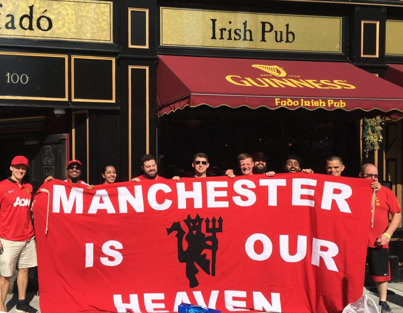 "MUFChicago members standing outside Fado Irish Pub holding up a sign that says ""Manchester is our Heaven"""