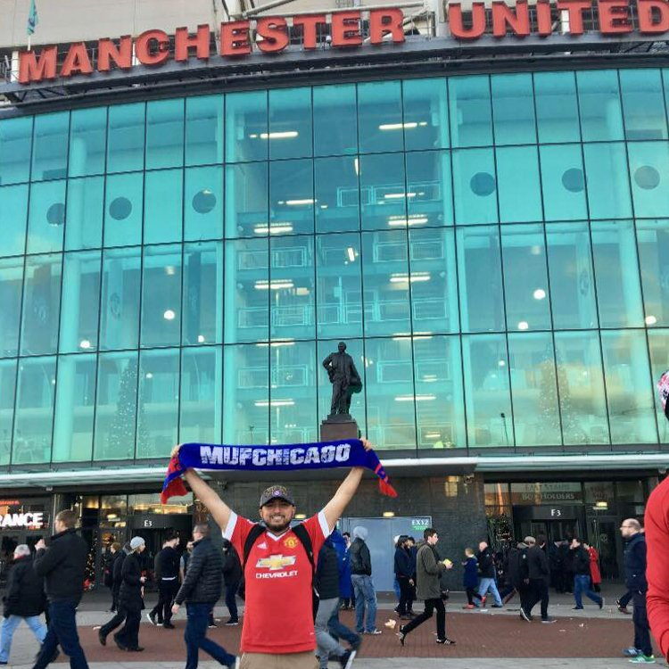 MUFChicago club member holding up custom diehard scarf in front of Manchester United Stadium