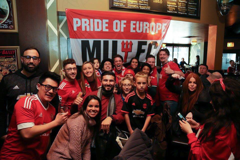 a group of women and men at a bar in front of a Manchester United Football Club flag