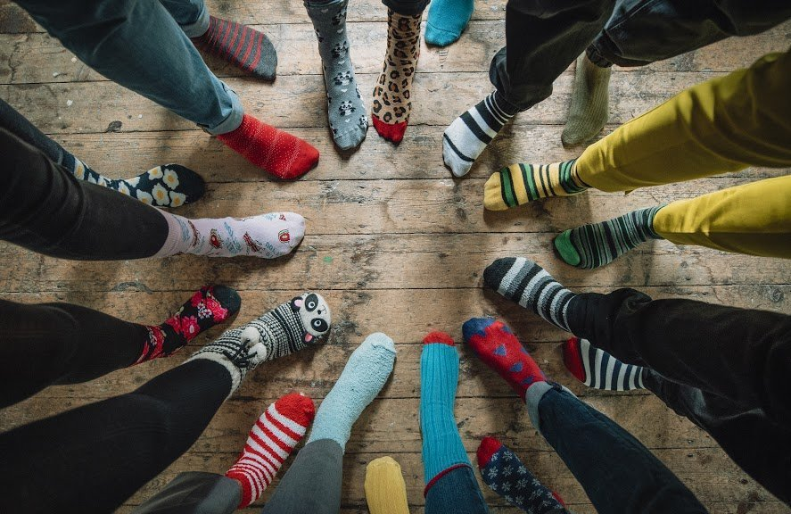overhead shot of people standing in a circle pointing their feet with custom socks on