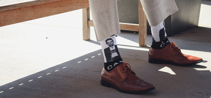Business casual man sitting on a bench wearing custom socks of someones mugshot on them.