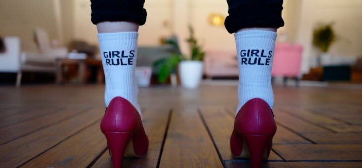 "Woman standing a living room wearing pink heals and white socks that say ""girls rule"" on the back of them in black text."