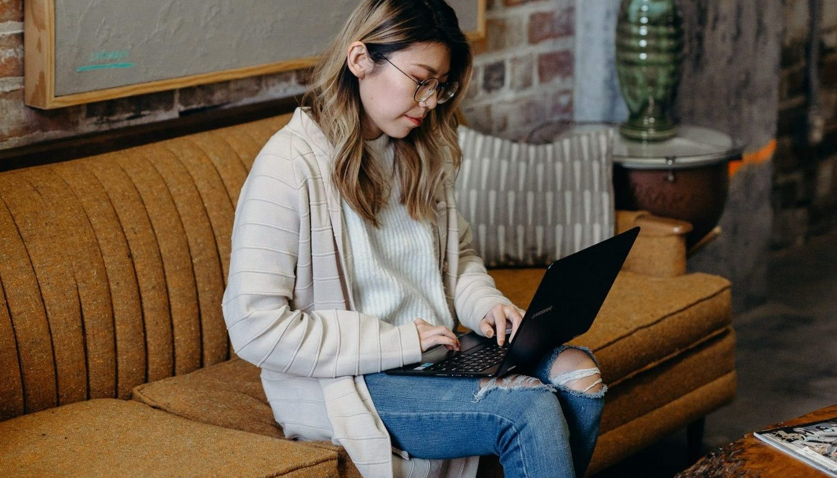 person sitting on couch in her living room on her computer practicing social distancing